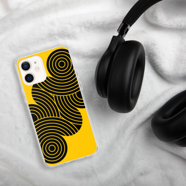 iphone case with an abstract design of black circles on a yellow background sitting next to headphones