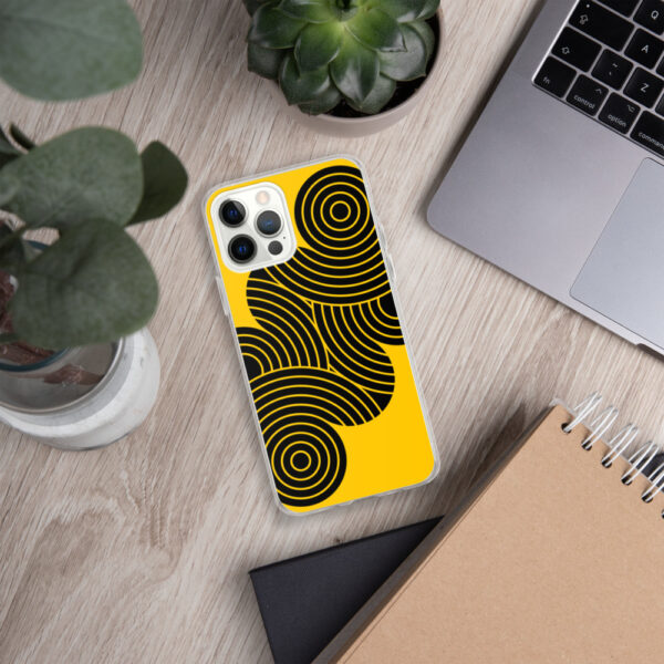 iphone case with an abstract design of black circles on a yellow background sitting next to a laptop