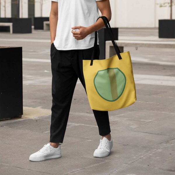 person holding a yellow tote bag with black handles and a minimalist green circle design