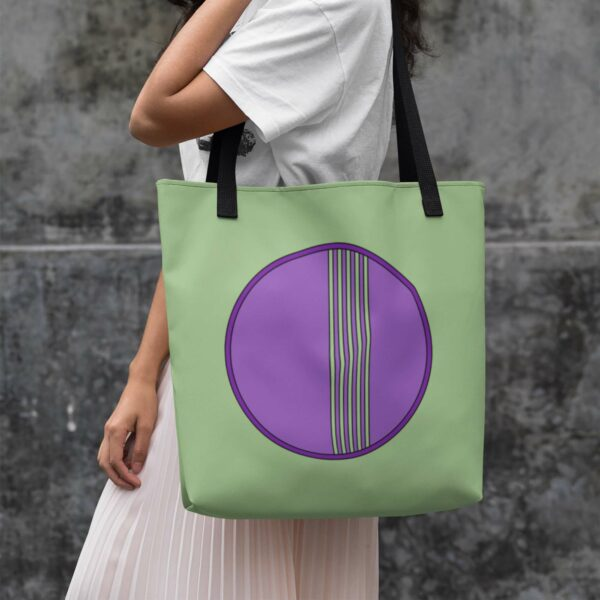 woman holding a light green tote bag with black handles and a minimalist purple circle design