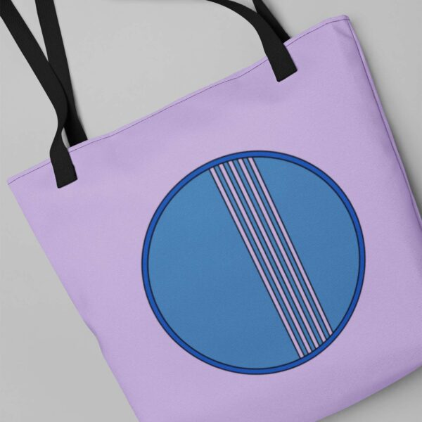 light purple tote bag with black handles and a minimalist blue circle design