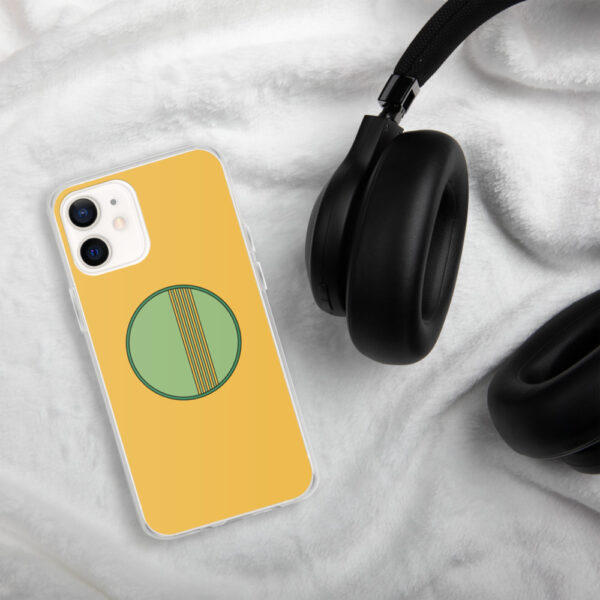 iphone case with a minimalist green circle design on a yellow background sitting next to headphones