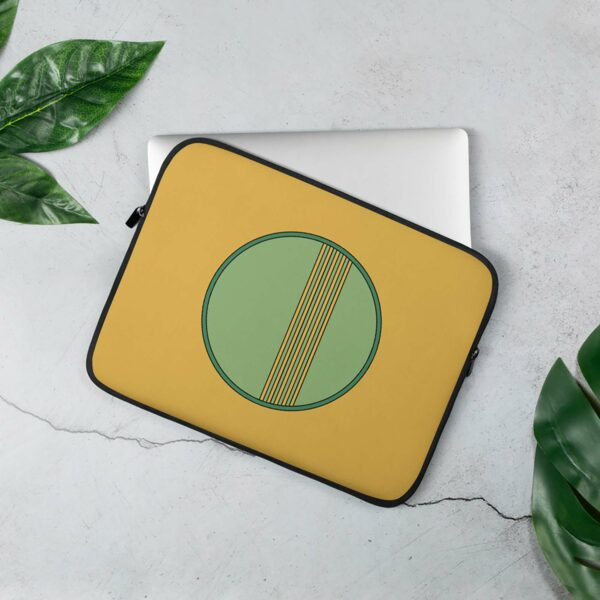 laptop sleeve with a minimalist green circle design on a yellow background sitting on a table