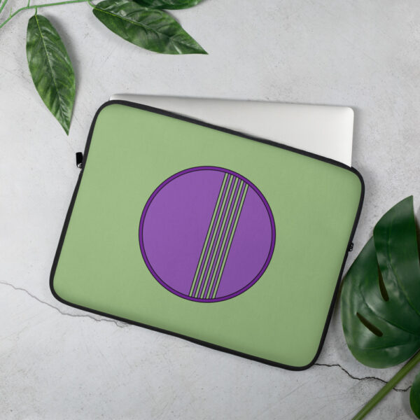 laptop sleeve with a minimalist purple circle design on a green background sitting on a table