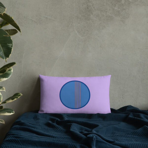 rectangle pillow with a minimalist blue circle design on a purple background sitting on a bed