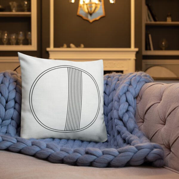 square pillow with a minimalist black circle design on a white background sitting on a sofa