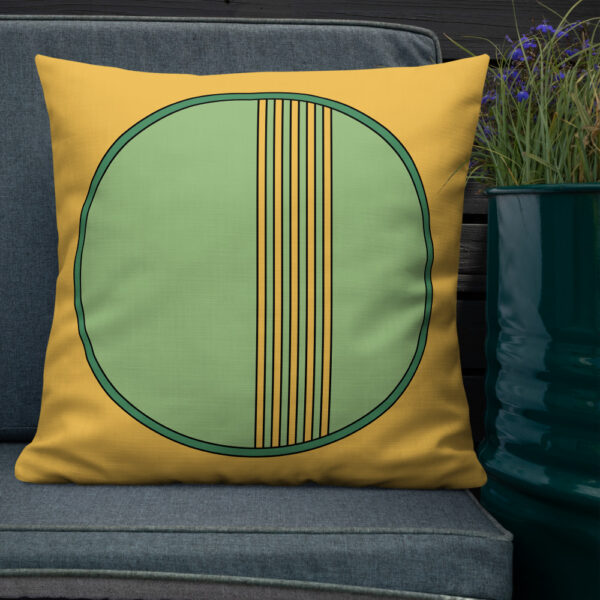 square pillow with a minimalist green circle design on a yellow background sitting on a chair next to a plant
