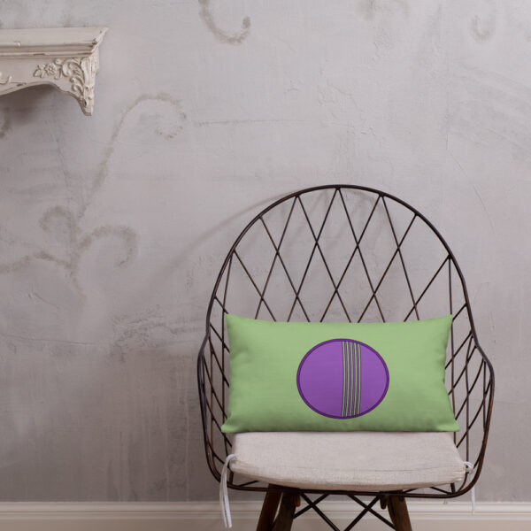 rectangle pillow with a minimalist purple circle design on a green background sitting on a chair
