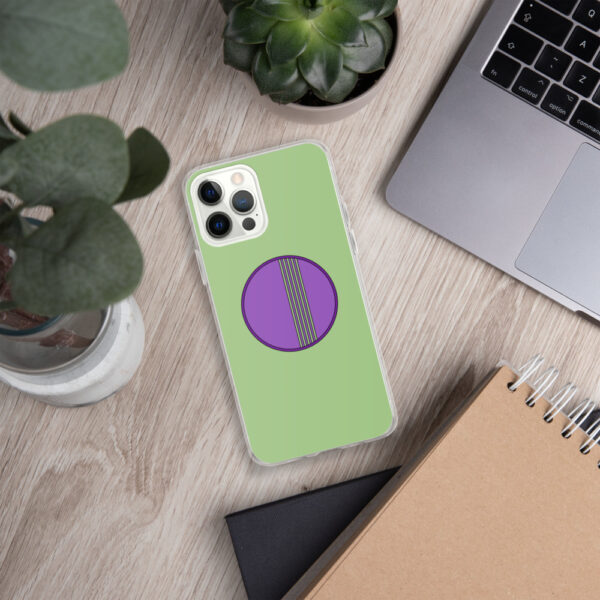 iphone case with a minimalist purple circle design on a green background sitting next to a laptop