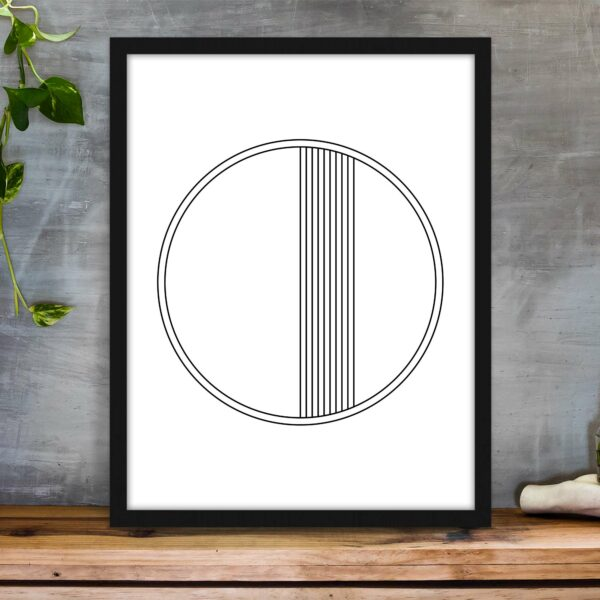 vertical fine art print of a black line circle on a white background in a black frame on a table