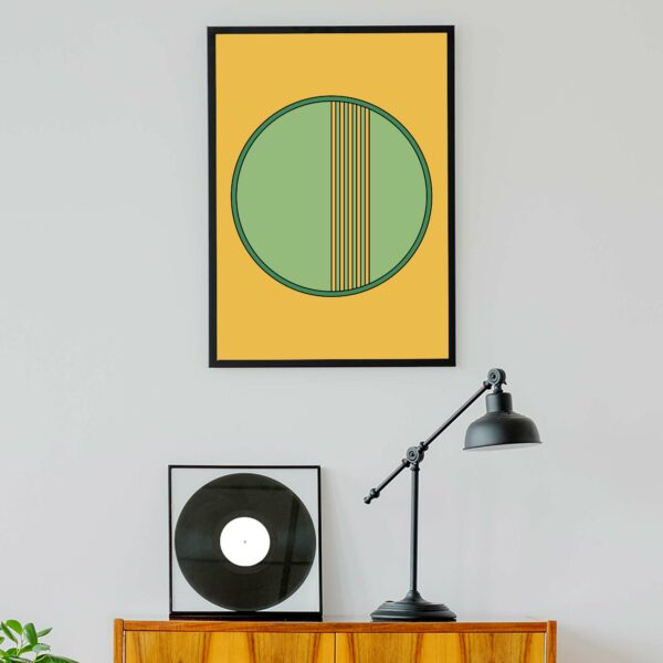 vertical fine art print of a green circle on a yellow background in a black frame hanging on a wall