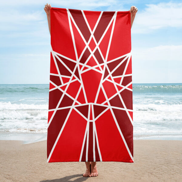 person on a beach holding a beach towel with a red maple leaf design
