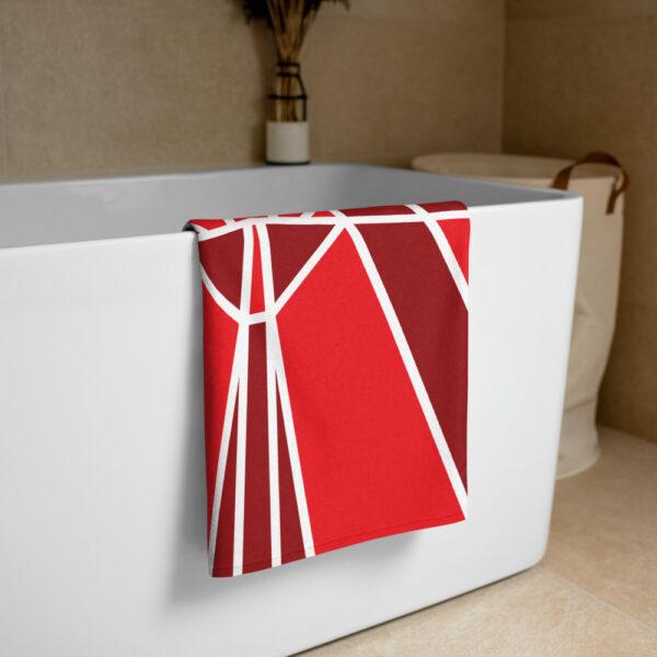 beach towel with a red maple leaf design draped over a bathtub