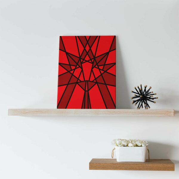 vertical stretched canvas art print with a red geometric maple leaf design sitting on a shelf