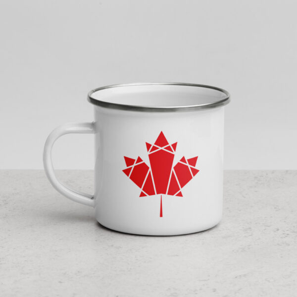 other side of a white enamel mug with a red geometric maple leaf design on the side