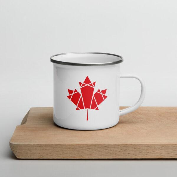 white enamel mug with a red geometric maple leaf design on the side sitting on a cutting board
