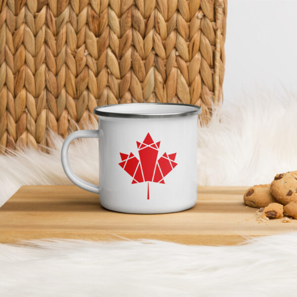 white enamel mug with a red geometric maple leaf design on the side sitting on a cutting board with cookies