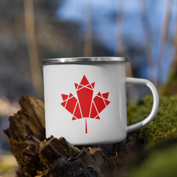 white enamel mug with a red geometric maple leaf design on the side sitting on a branch
