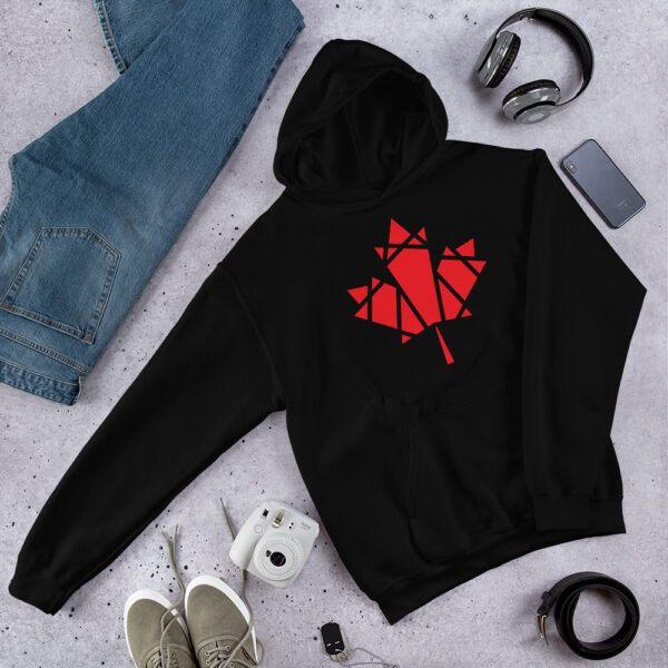 black hooded sweatshirt with a geometric red maple leaf design on the chest on a table next to jeans