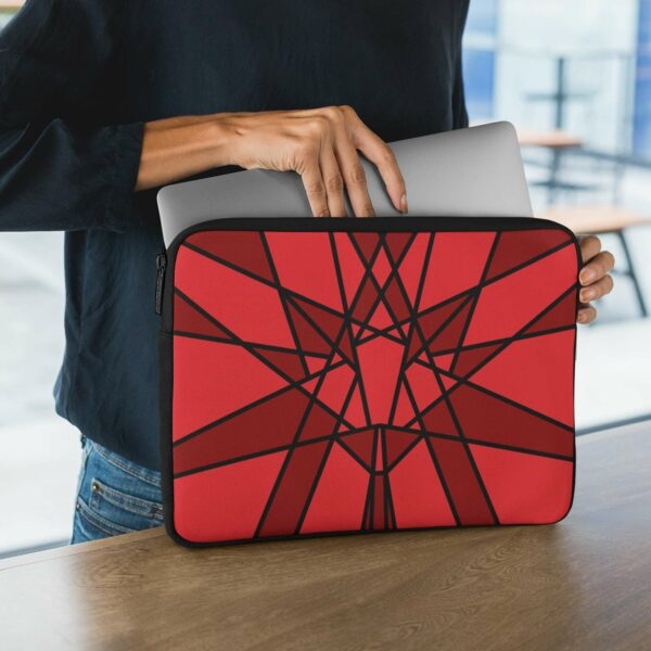 person holding a laptop sleeve with a geometric red maple leaf design