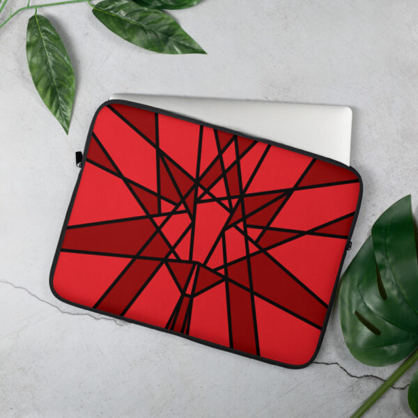 laptop sleeve with a geometric red maple leaf design sitting on a table