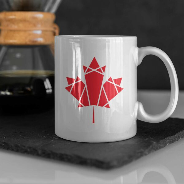 11 ounce white ceramic coffee mug with a red geometric maple leaf design on the side sitting on a table