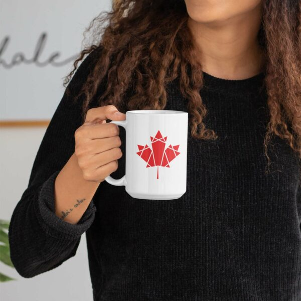 woman holding a 15 ounce white ceramic coffee mug with a red geometric maple leaf design on the side