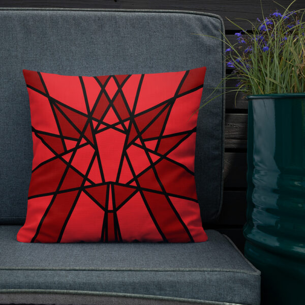 square pillow with a geometric red maple leaf design sitting on a chair next to a plant