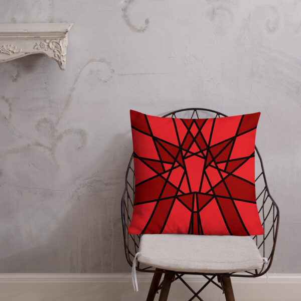 square pillow with a geometric red maple leaf design sitting on a chair