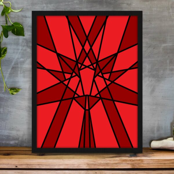 vertical fine art print with a geometric red maple leaf design in a black frame on a table