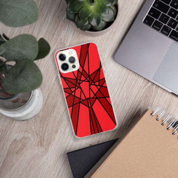iphone case with a geometric red maple leaf design sitting next to a laptop